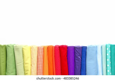 Rolls of colored fabrics lined for the colors of the rainbow.