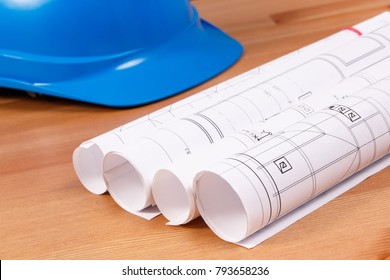 Rolls of diagrams or electrical construction drawings and protective blue helmet for engineer jobs, technology concept