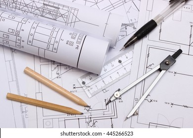 Rolls of electrical diagrams and accessories for drawing lying on construction drawing house