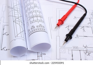 Rolls of electrical diagrams and cables of multimeter lying on construction drawing of house, drawings and tools for engineer jobs