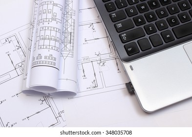 Rolls of electrical diagrams with construction drawings of house and laptop, drawings for projects engineer jobs