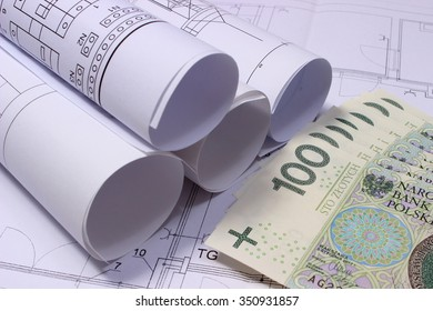 Rolls of electrical diagrams and heap of banknotes lying on construction drawing of house, drawings for the projects engineer jobs, concept of payment for project
