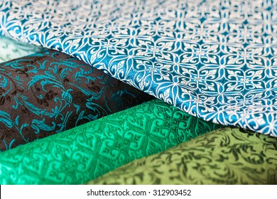 Rolls of fabric and textiles in a factory shop. Multi different colors and patterns on the market