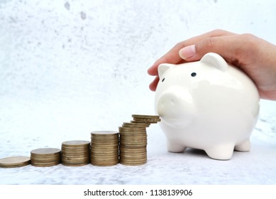 Rolls of gold coin money lead to white piggy bank with hand placed on top