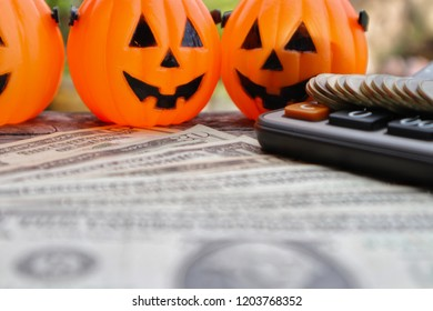 Rolls gold coin money on calculator with pumpkin buckets and blur Dollar banknote