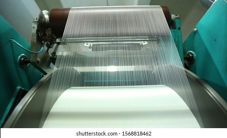 Rolls of industrial cotton fabric for clothing cloth textile manufacture on machine Fibre thread lines on the weaving loom machine. A loom machine for clothing or woven clothes. Weaving machine for ga