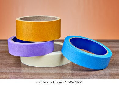 Rolls of multi-colored paper and plastic adhesive tape lie on the table.