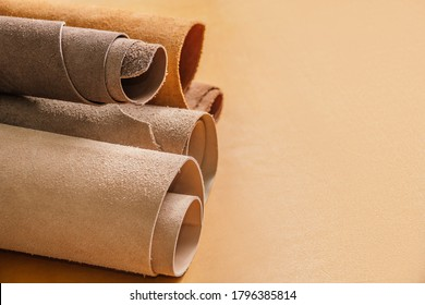 Rolls of natural brown and beige leather. Materials for leather craft. On yellow background