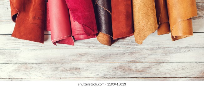 Rolls of natural color leather. Materials for leather craft. Copy space. Multi colored leather in rolls. Top view. Handmade craft. Different samples of leather on wooden table