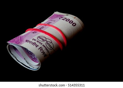 Rolls of the new indian currency. These Rs. 2000 notes are isolated on black and were introduced to curb black money