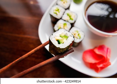 Rolls in nori seaweed with avocado, pickled ginger and soy sauce. Asian cuisine, traditional dish - sushi.