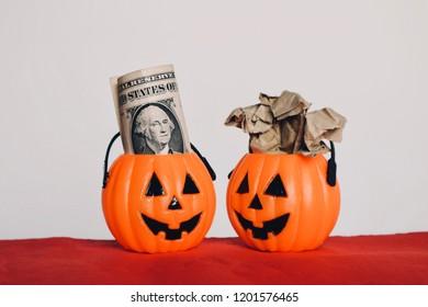 Rolls of old Dollar money with crumpled paper inside orange pumpkin buckets on red background