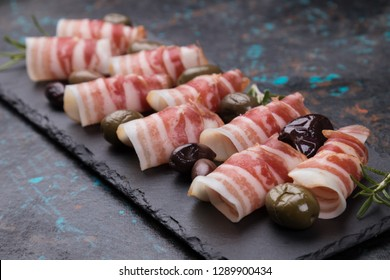 Rolls of pancetta bacon served with pickled olives, popular antipasto food