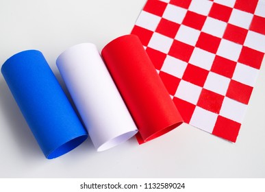 Rolls of paper, blue, white, and red placed over a checkered pattern paper on a white background. The image giving senses of colorfulness and the flags of France and Croatia.
