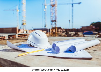 Rolls of paper with building plans and hardhat on wooden surface at construction site