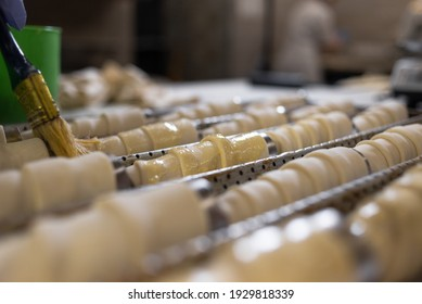 Rolls of raw puff pastry on a metal cone are smeared with a brush with vegetable oil. Baking in a pastry shop. Bakery and flour products.