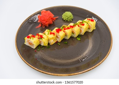 Rolls with red fish, cheese and caviar of red fish laid out on a plate with wasabi and ginger. Japanese and Chinese cuisine.