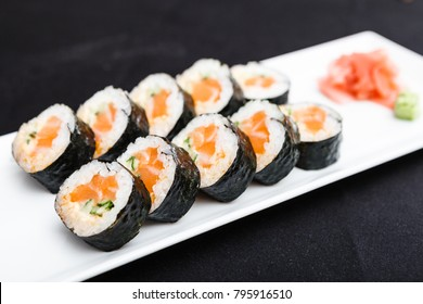 Rolls with salmon, cucumber and flying fish roe served on a plate