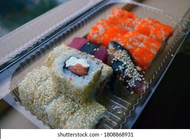 Rolls with salmon in white sesame seeds on the windowsill. Sushi, food.