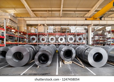 Rolls of sheet metal lie on the floor. Internal warehouse of raw materials.