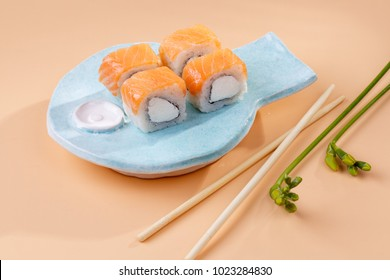 rolls and sushi on a plate in the form of fish. on a homogeneous background of peach color