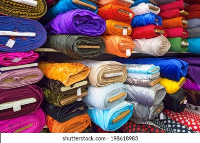 Rolls of textile, cloth and tissue of various colours on the market