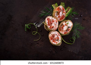 Rolls of thin pancakes with salmon, horseradish cream cheese. Black old background. Selective focus. Top view