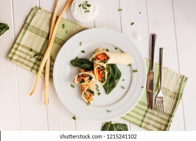 Rolls of thin pancakes with smoked salmon, horseradish cream cheese and spinach leaves. Side view with copy space.