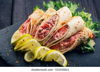 Rolls of thin pancakes with smoked salmon on dark background