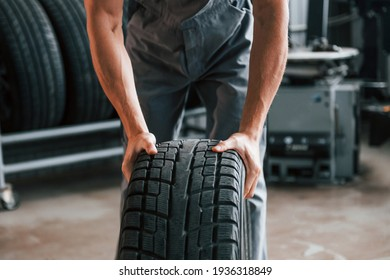Rolls the tire. Adult man in grey colored uniform works in the automobile salon.