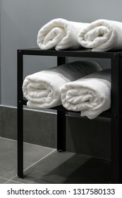 Rolls of white towels on an open metal rack in a hotel bathroom