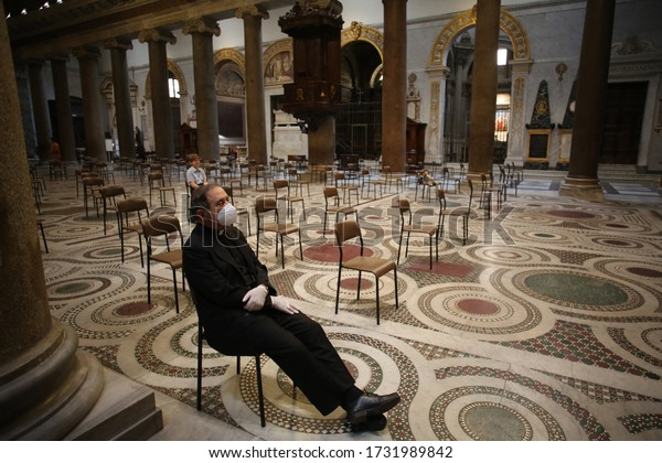 Roma, Italy 9 may 2020: Priest with mask in church in social distancing in Santa Maria in Trastevere. The first weekend to start phase 2 in Italy after the Covid-19 emergency quarantine.