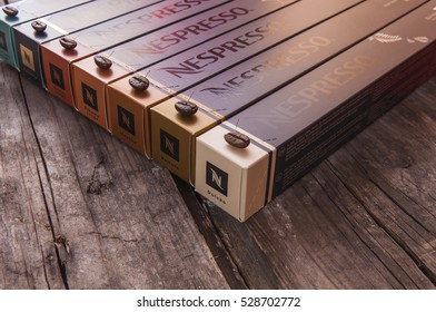 ROMA - ITALY - DECEMBER 04, 2016: Nespresso boxes on wooden surface with coffee beans on top of each box, extremely shallow depth of field