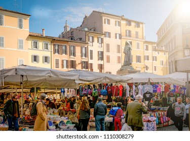Roma, Italy, march 2017: people looking at fruits and vegetables for sale in the historic Campo de Fiori market with the Giordano Bruno statue in the background in Rome, Italy
