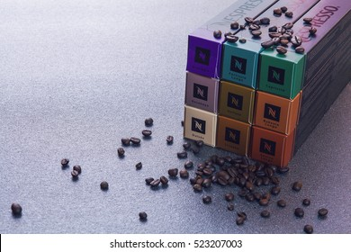 ROMA, ITALY - NOVEMBER 25, 2016: six packs of nespresso capsules on gray table with coffee beans, dramatic light from behind, extremely shallow depth of field