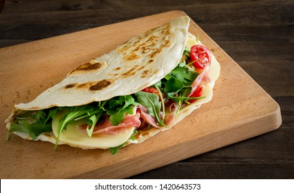 Romagna piadina filled with cheese,ham,tometoes and rocket  on chopping board