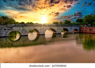 Roman ancient tiberius and augusto bridge over marecchia river in Rimini Italy at sunset or sunsrise