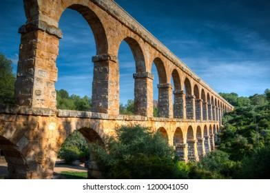Roman Aqueduct (Pont del Diable) in Tarragona, Catalonia, Spain on a sunny summer afternoon