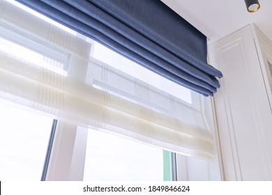 Roman blind in the interior detail close-up. Curtain blue blackout fabric, sheers white linen, fashionable modern window decoration design at home