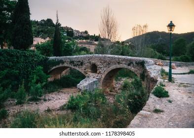 The Roman bridge across the Torrent de Sant Jordi at Pollenca in Mallorca at sunset.