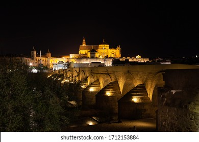 The Roman bridge of Córdoba, also known as Old bridge, over Guadalquivir river at night. The Mosque-Cathedral of Córdoba is also seen.
