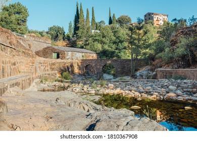 Roman bridge and natural pool in Las Mestas, Caceres, Extremadura, Spain - Shutterstock ID 1810367908