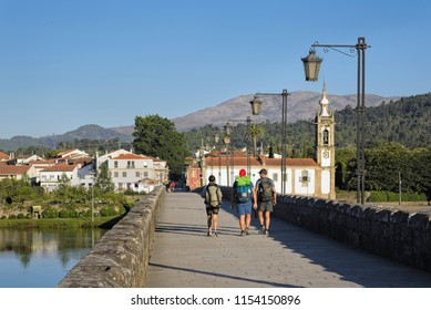 Roman bridge in Ponte de Lima,with three hikers on the way. Beautiful historic stone supported by the architecture of its arches. Typical old lamps in Portugal, and the Santo António da Torre church