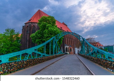 Roman Catholic parish Saint Mary church NMP on Sand island Wyspa Piasek, view through arch of Tumski bridge over Odra Oder river in old town historical city centre of Wroclaw, evening view, Poland - Shutterstock ID 1548322460