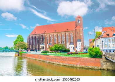 Roman Catholic parish Saint Mary church NMP on the Sand island Wyspa Piasek and Mill Mlynski bridge over Oder Odra river in old historical city centre of Wroclaw, Poland - Shutterstock ID 1555482365
