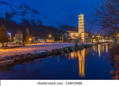 Roman Catholic St. Karl Church in St.Moritz-Bad in Switzerland at night on the shores of Lake St. Moritz Illuminated Building Tower with Reflection under clear blue sky in Spring
