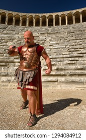 Roman Gladiator with sword in sun on stage at the ancient Aspendos theatre Aspendos, Antalya, Turkey - November 8, 2012