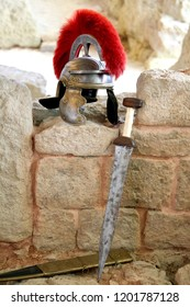 "Roman guard helmet with red crest, and short sword or ""gladius"", leaning on a stone wall"