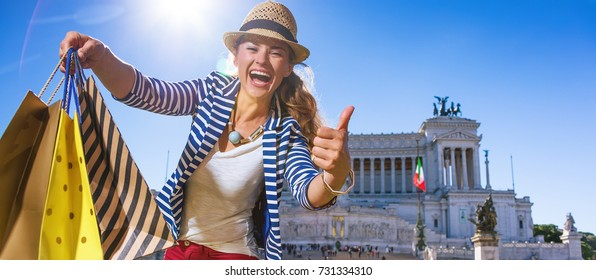 Roman Holiday. happy modern tourist woman with shopping bags in the front of Palazzo Venezia in Rome, Italy showing thumbs up