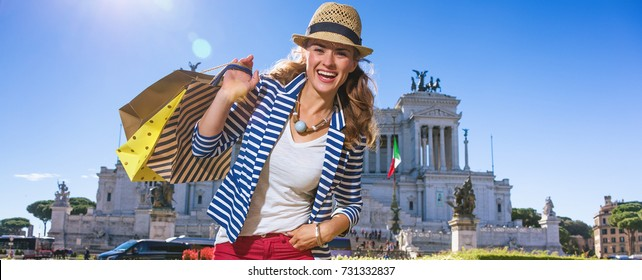 Roman Holiday. Portrait of happy young woman at Piazza Venezia in Rome, Italy with shopping bags